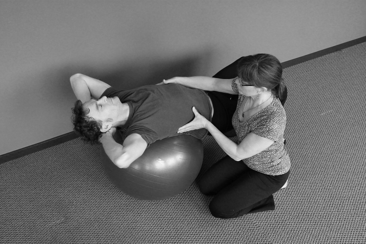 Instructor Jaci Metivier is working hands-on with a client in extension on a large ball